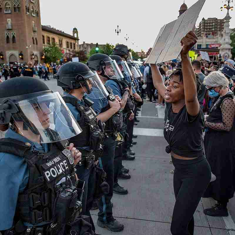 woman holding a protest sign in front of police